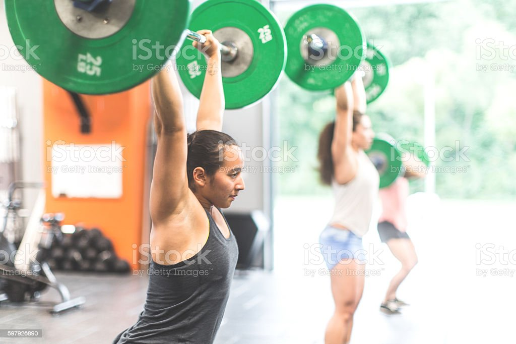 Women doing weightlifting during a cross training workout stock photo