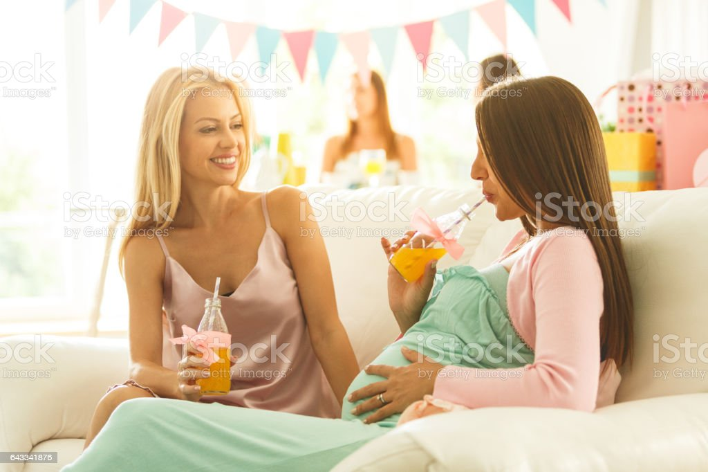 Women drinking juice on baby shower party stock photo