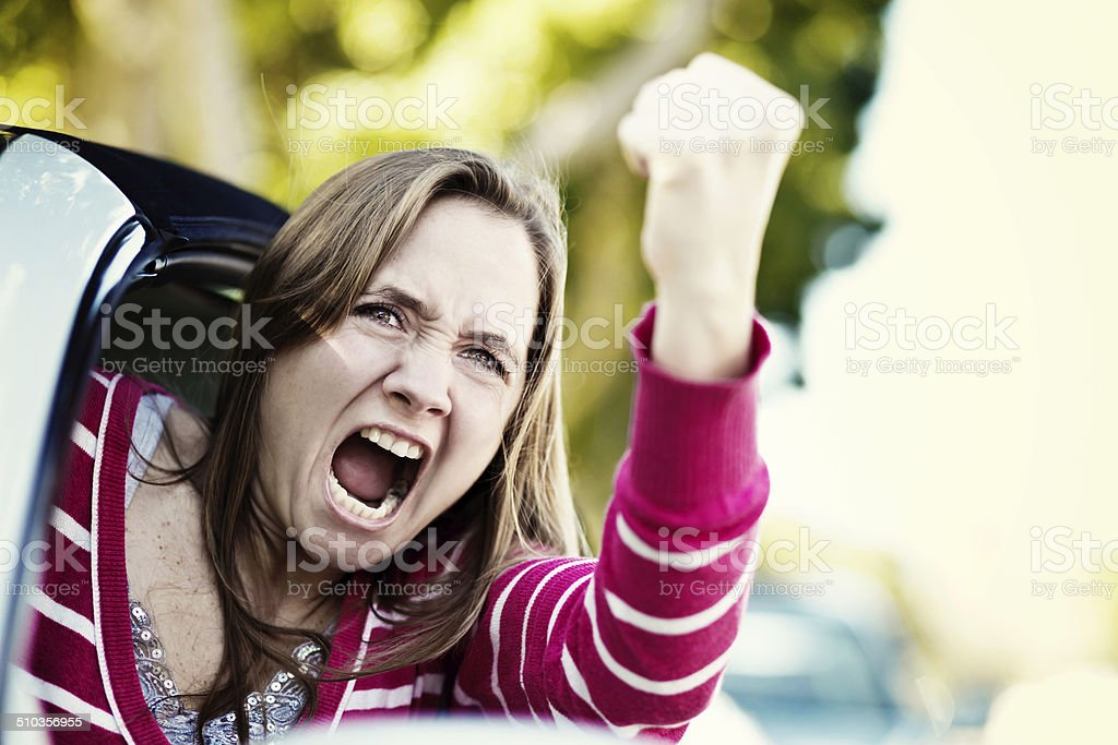 Women drivers get road rage too! Furious female shaking fist stock photo