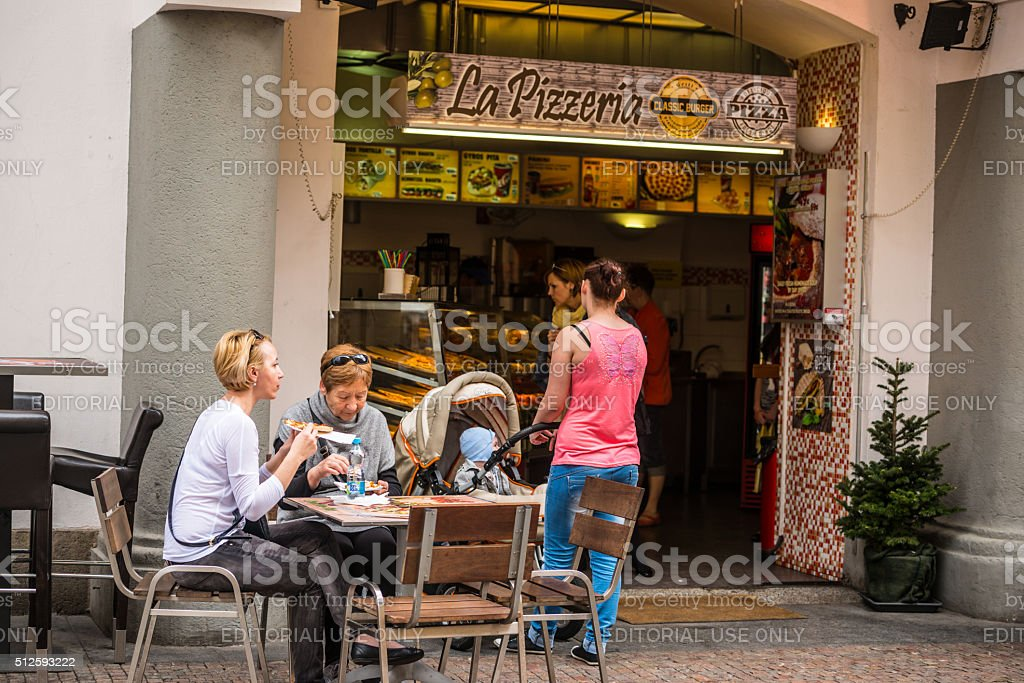 Women eating pizza outdoors in Prague stock photo