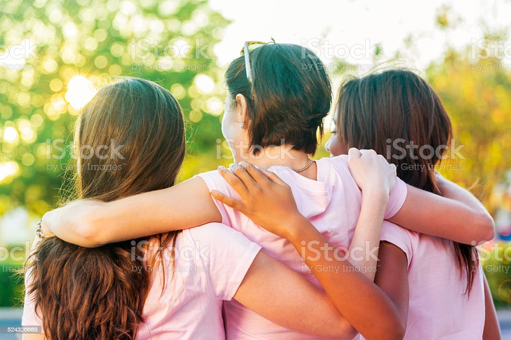 Women embracing after finishing breast cancer awareness race stock photo