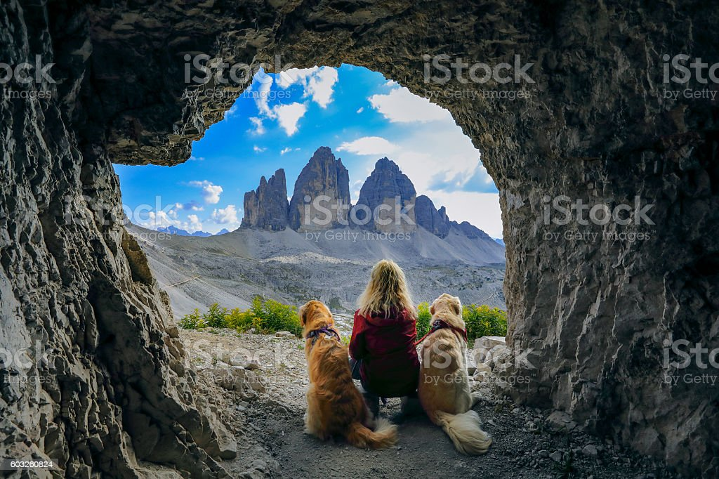 Women enjoy the view with dogs out of cave, Dolomites stock photo