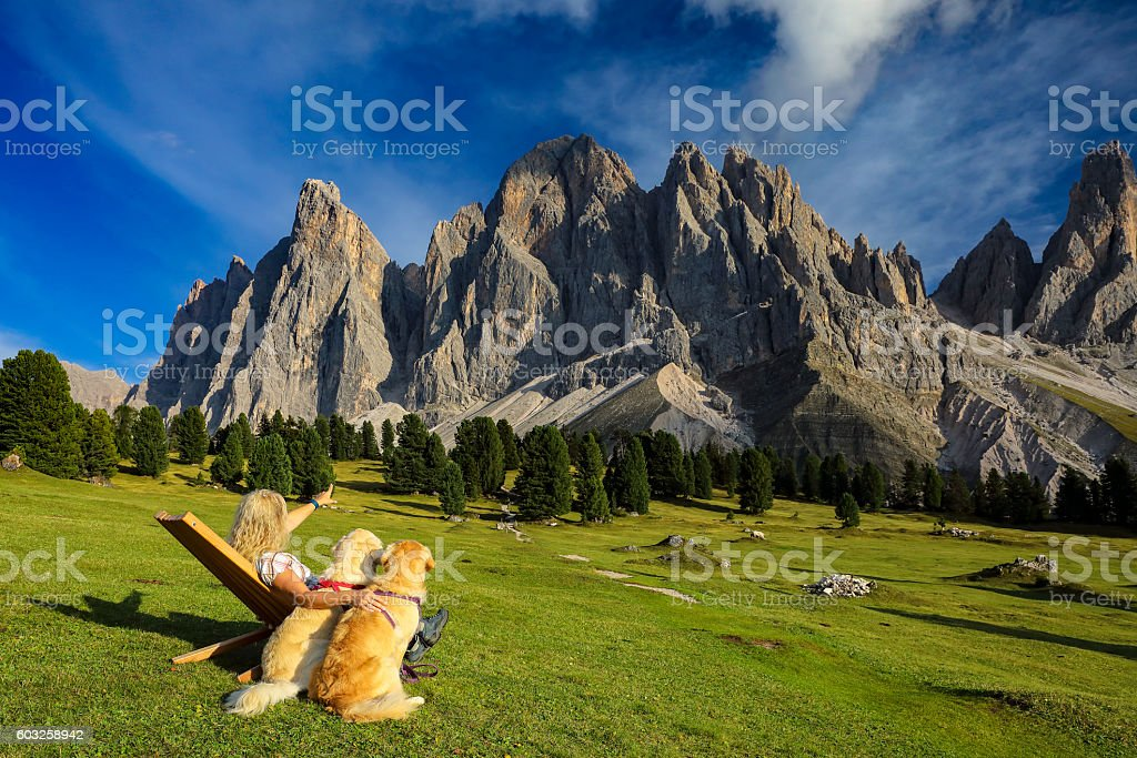 Women enjoy the view with her dogs, Geisler Gruppe, Alps stock photo