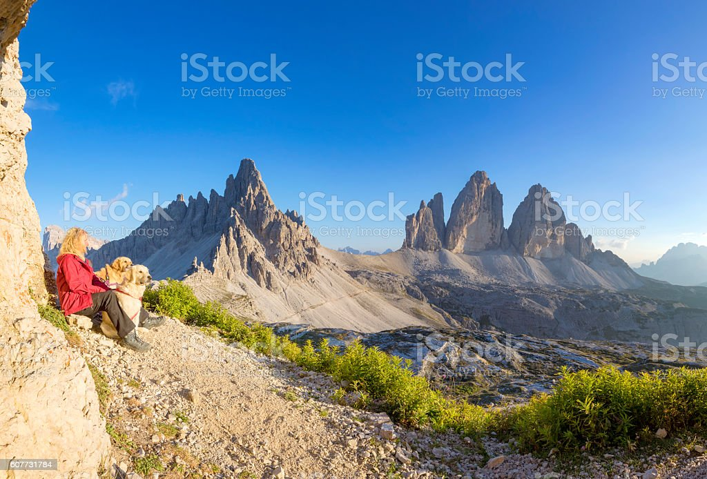 Women enjoy view with her dogs to Tre Cime, Dolomites stock photo