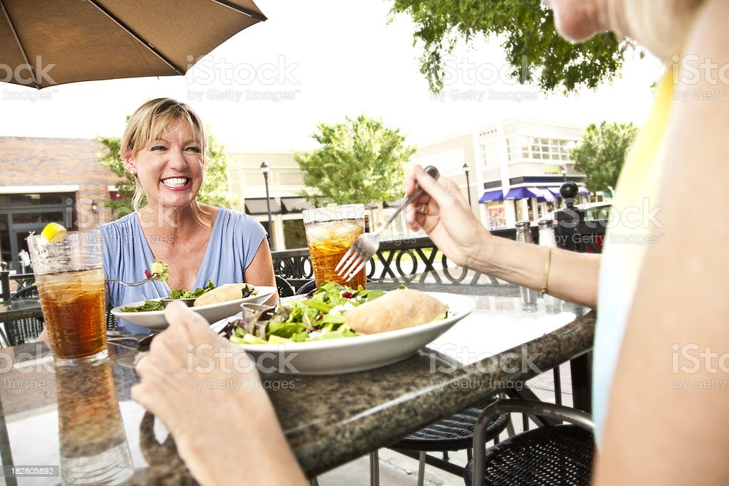 Women Enjoying Lunch Together on Outside Restaurant Patio royalty-free stock photo