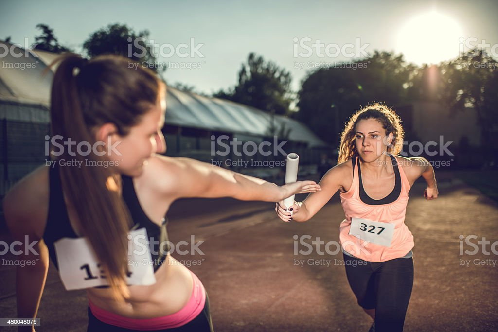 Women exchanging relay baton on a sports race. stock photo