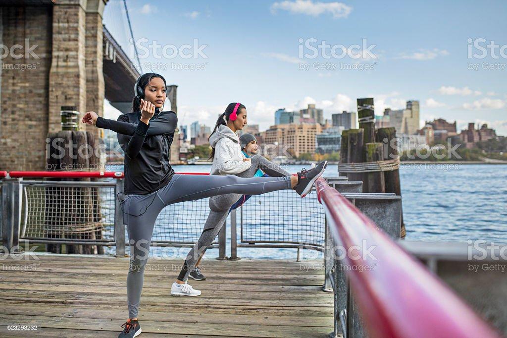 Women exercising on boardwalk by Brooklyn Bridge stock photo