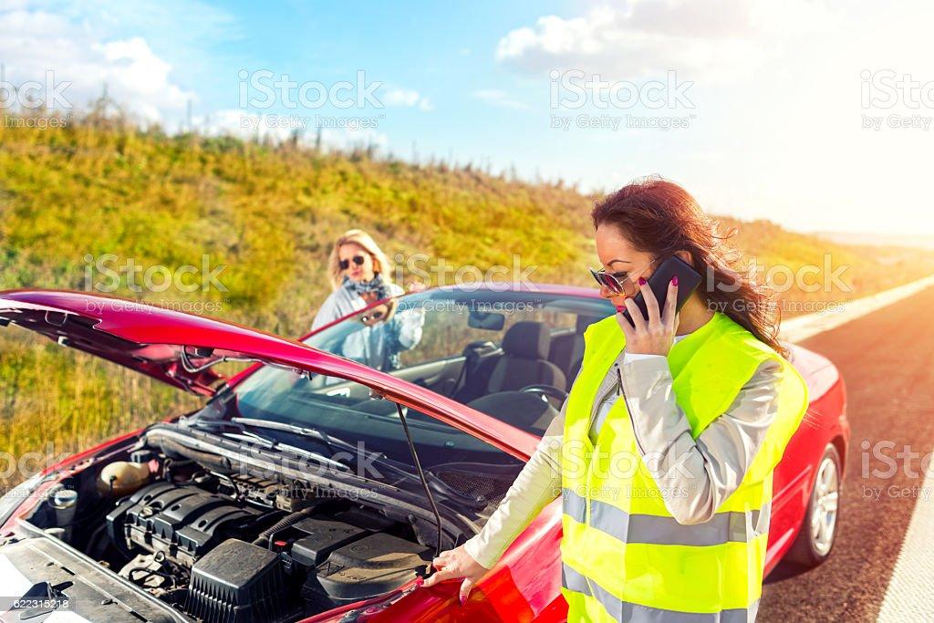 Women experiencing vehicle breakdown on roadside stock photo