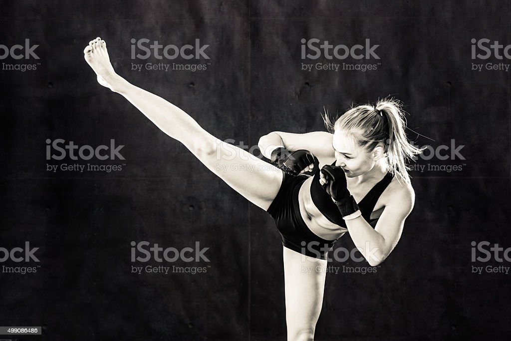 Women Fighter Kicking In Black and White stock photo