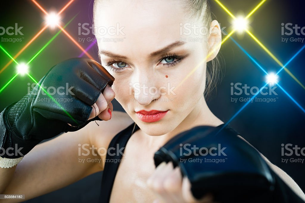 Women Fighter Posing With Arena Lighting Flares in the Background stock photo
