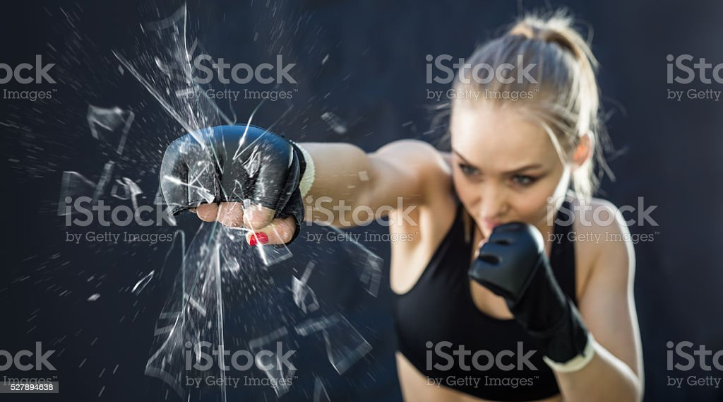 Women Fighter Punching Close Up Glass Shattering stock photo