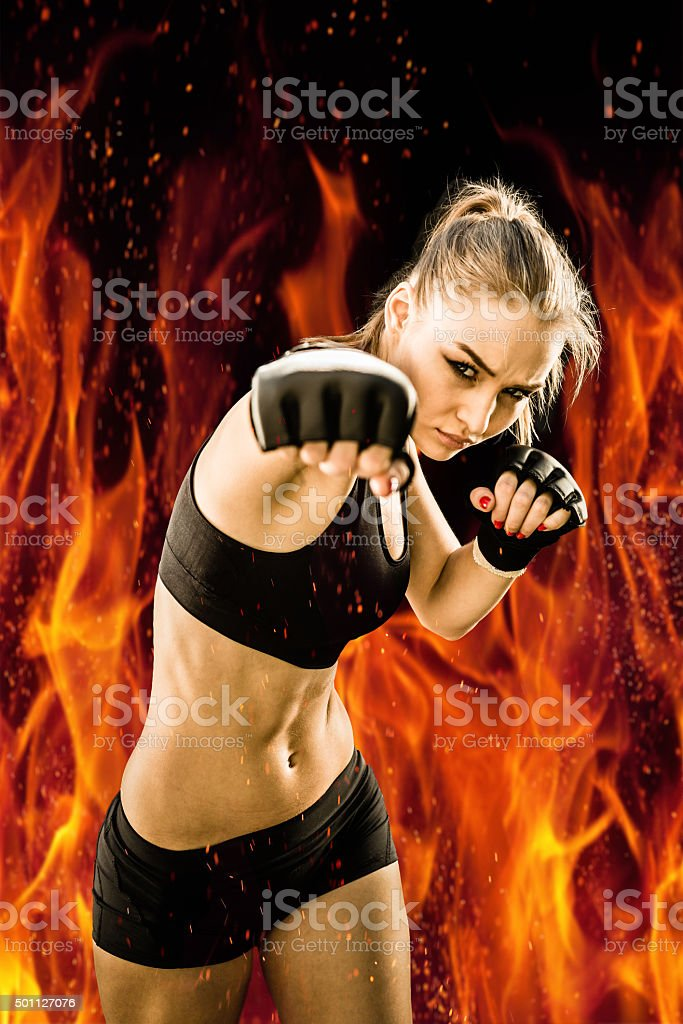 Women Fighter Throwing a Punch with a Fire Background stock photo