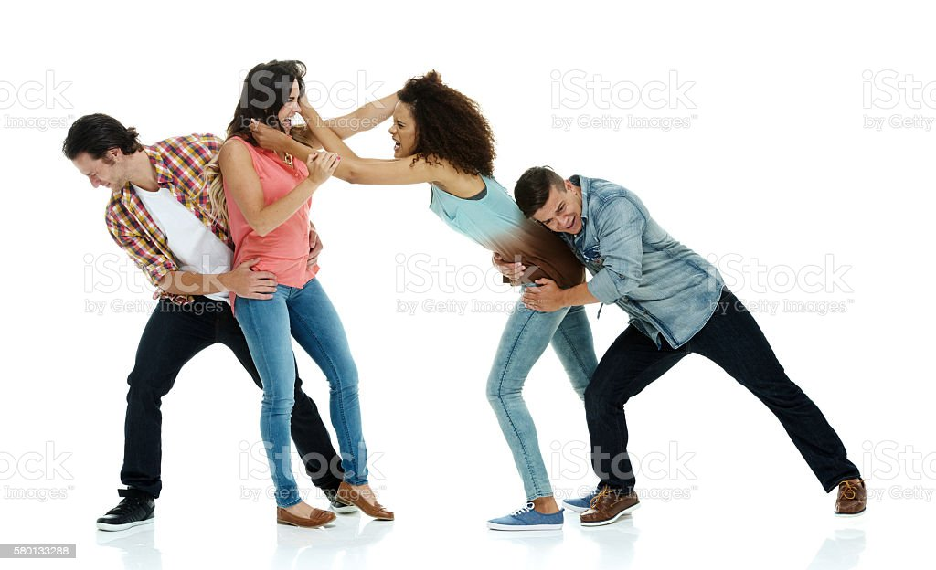 Women fighting while men hold them back stock photo