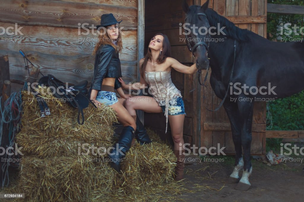Women flirt on farm, the horse stands nearby. stock photo