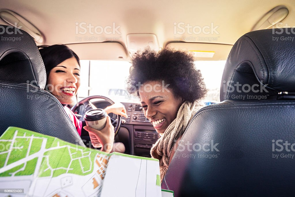 Women friends in the car looking the road map stock photo