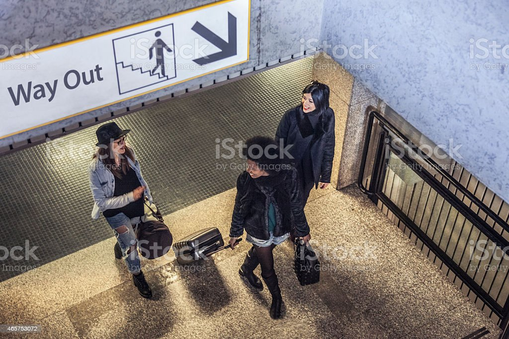 Women friends leaving the train station stock photo