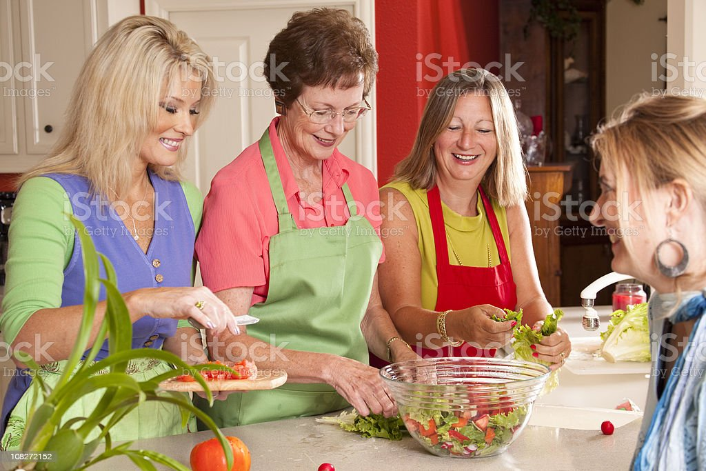Women friends preparing salad for a luncheon meal. Home kitchen. stock photo