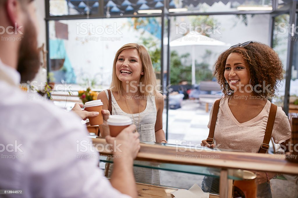Women friends receiving their hot drinks at cafe stock photo