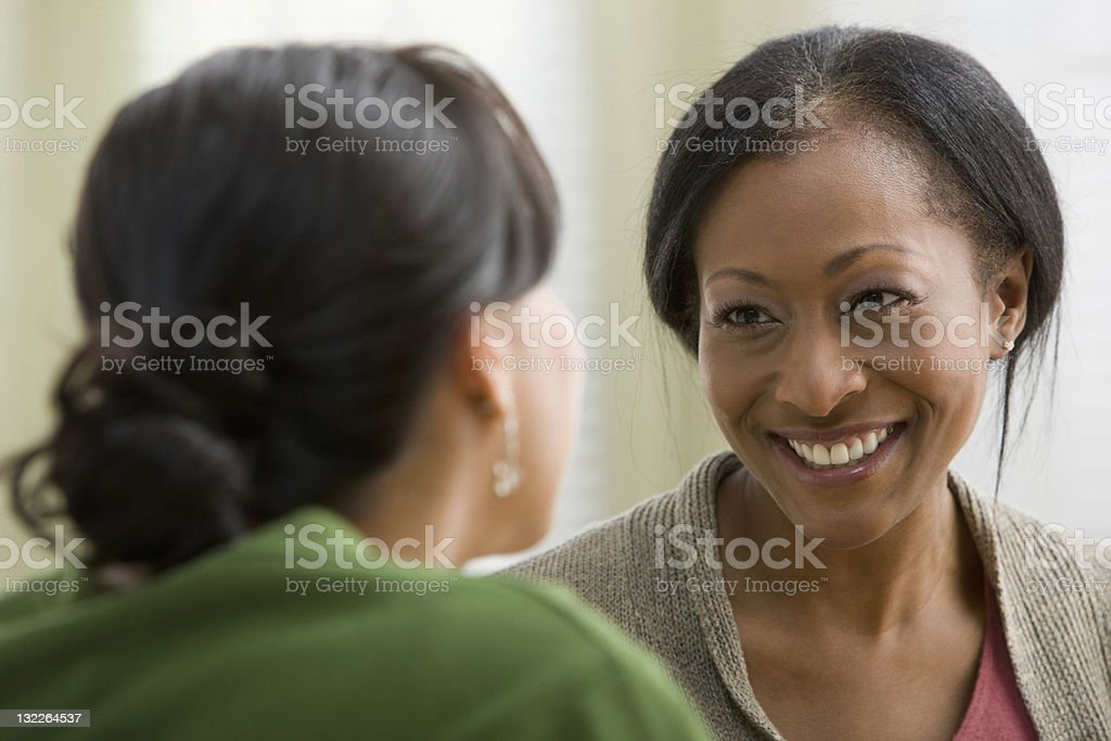 Women friends smiling at each other stock photo