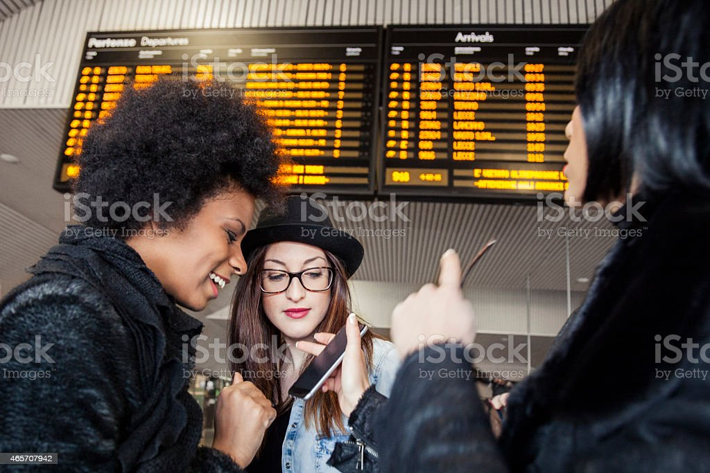 Women friends waiting for the train in the station stock photo