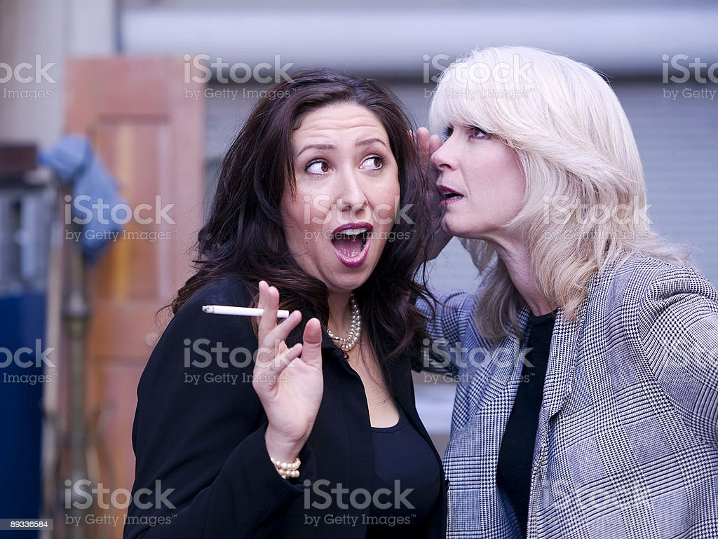 Women Gossip During a Smoking Break stock photo