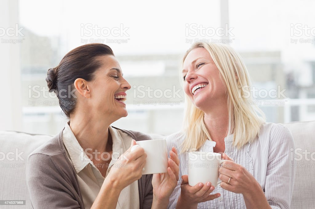 Women gossiping while having coffee in living room stock photo