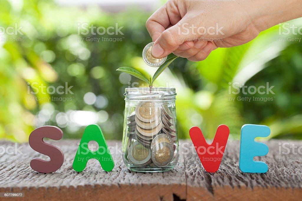 women hand putting money coin in jar. ฅ stock photo