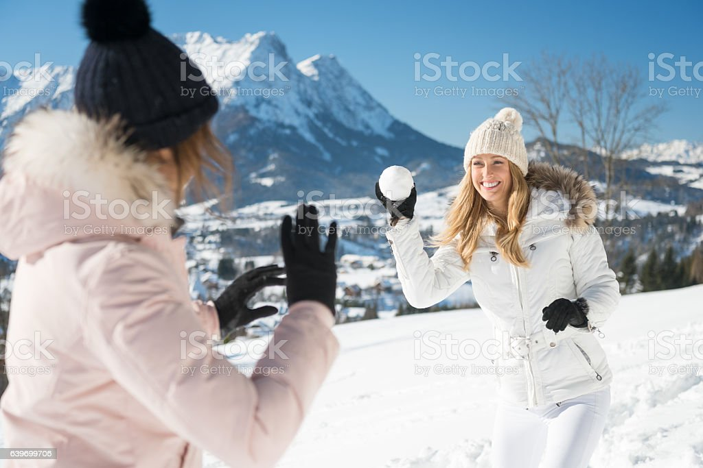 Women having a friendly Snowball Fight, Austrian Alps Panorama stock photo