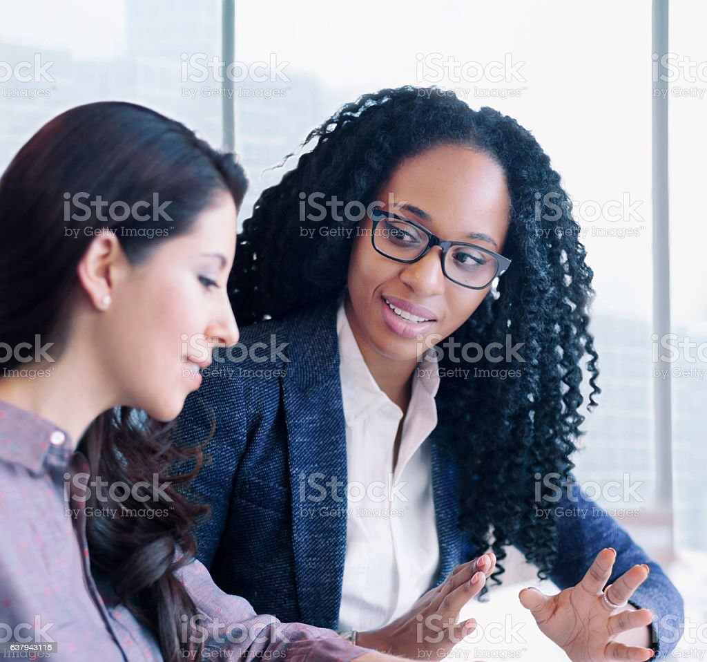 Women having conversation together in business office stock photo