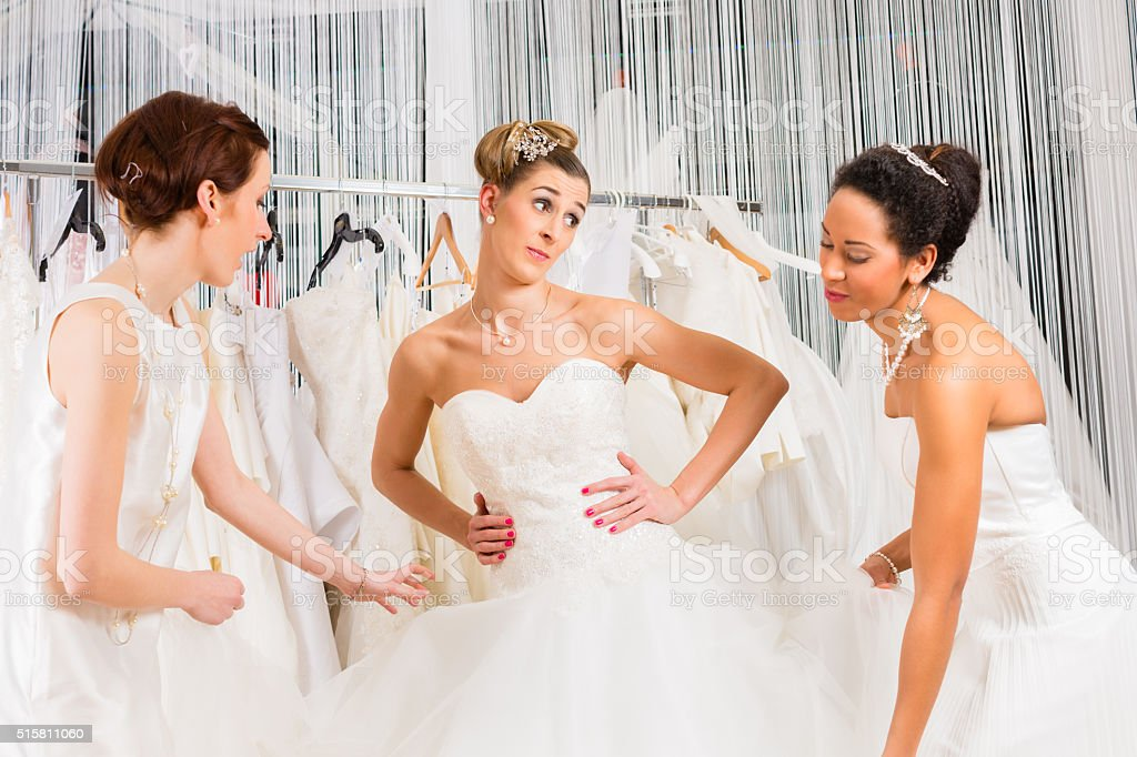 Women having fun during bridal dress fitting in shop stock photo