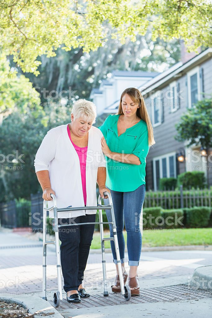 Women helping her mother use walker stock photo