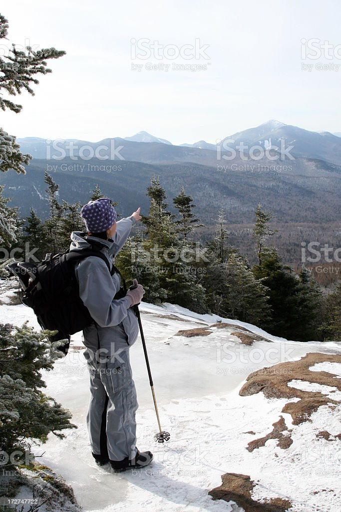 Women Hiker Pointing a Mountain Summit in Winter stock photo