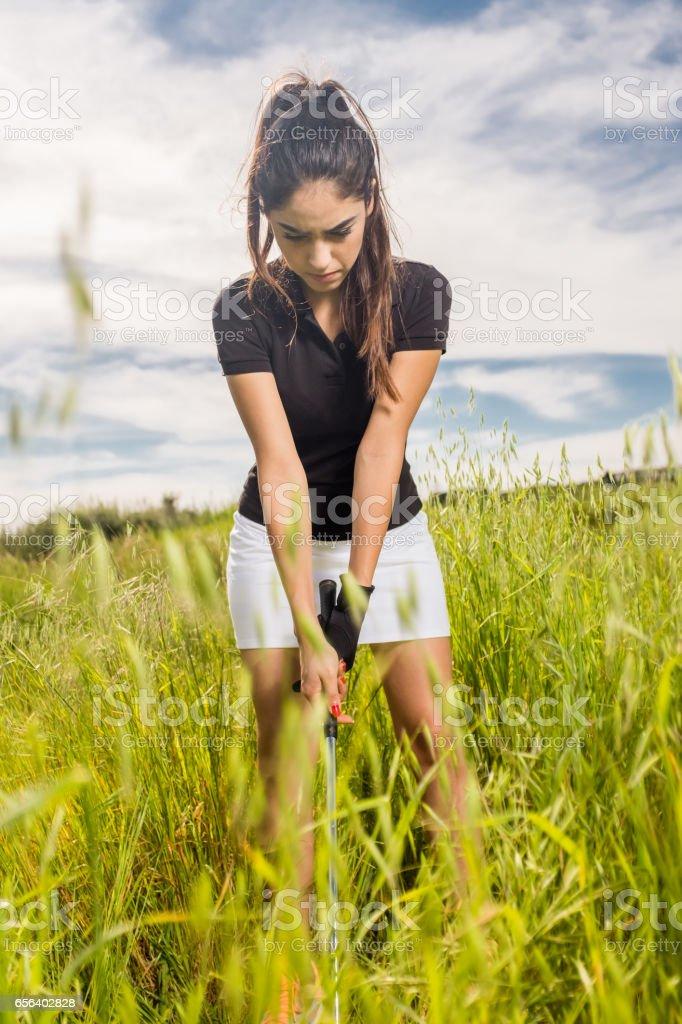 Women Hitting A Golf Ball Out Of Tall Grass stock photo