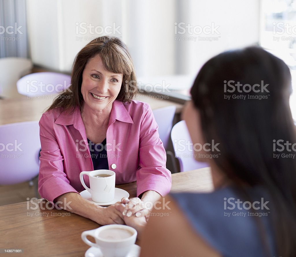 Women holding hands in cafe stock photo