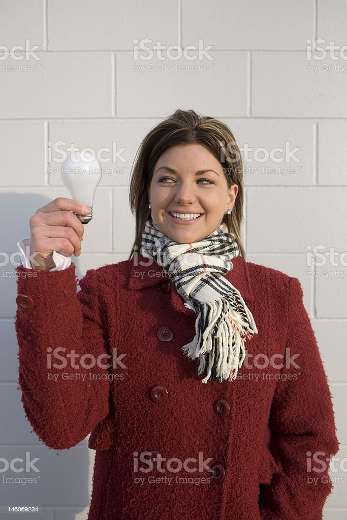 Women Holding Light Bulb While Smiling royalty-free stock photo