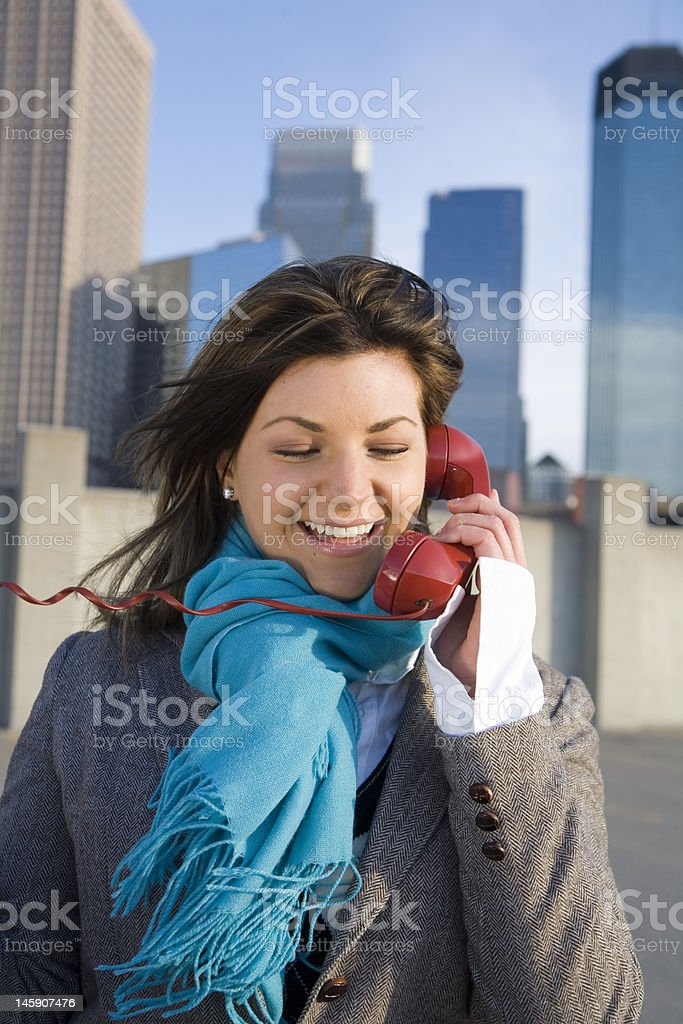 Women holding old telephone outside in urban setting. royalty-free stock photo