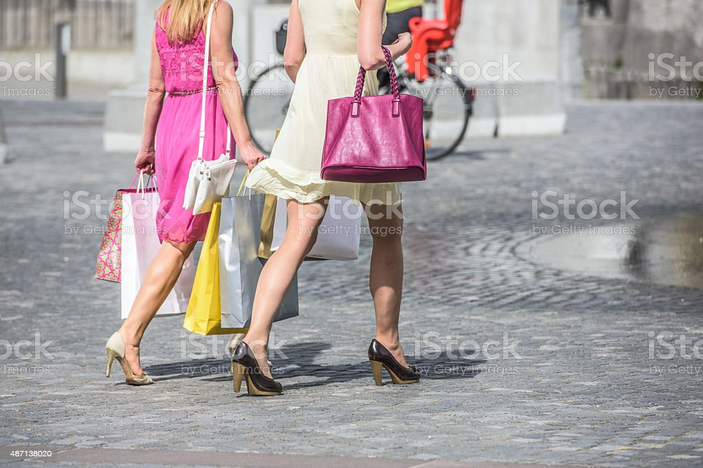 Women holding shopping bags and walking stock photo