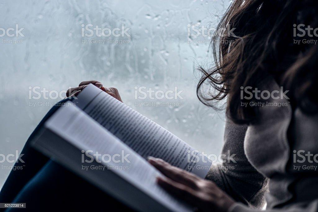 Women how Reading Book next to Window While Raining stock photo