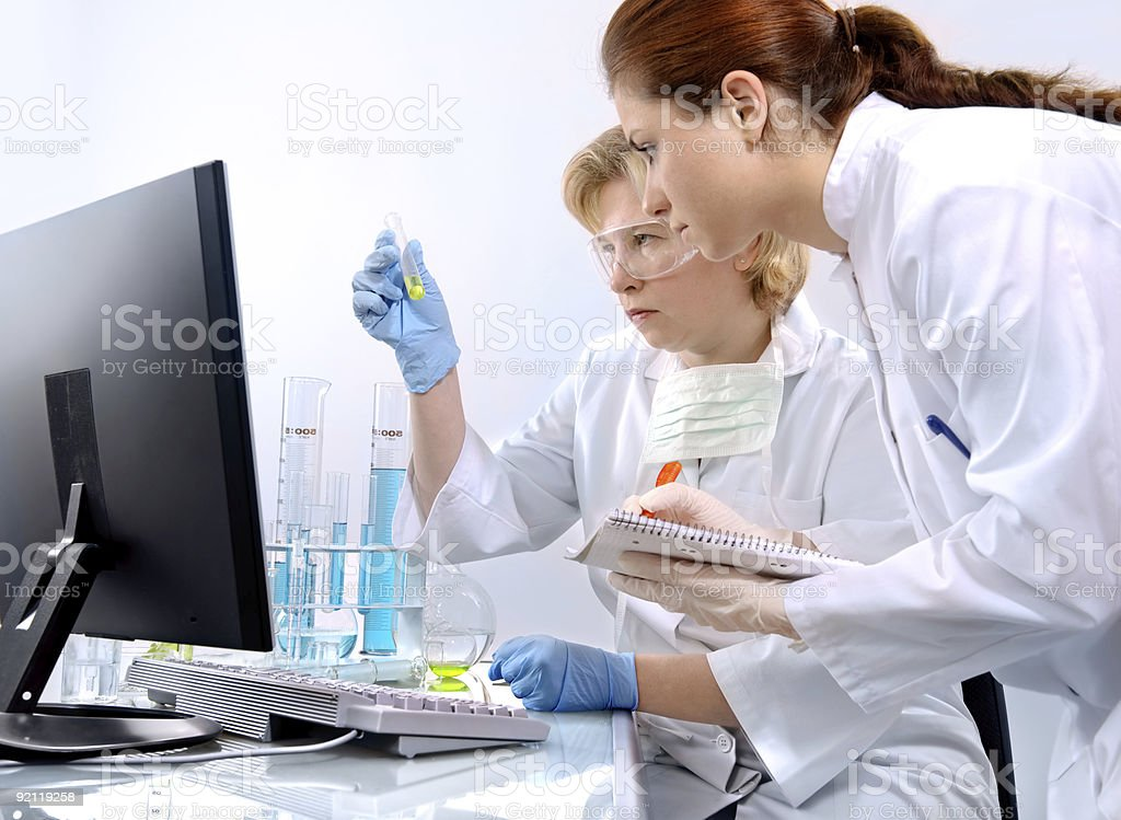 Women in a laboratory examining test tubes and taking notes royalty-free stock photo