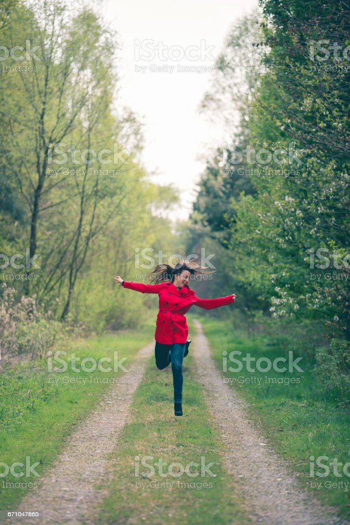 Women in a red coat running stock photo