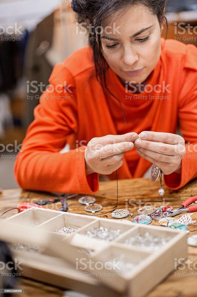 Young woman creating handmade jewelry in her studio.