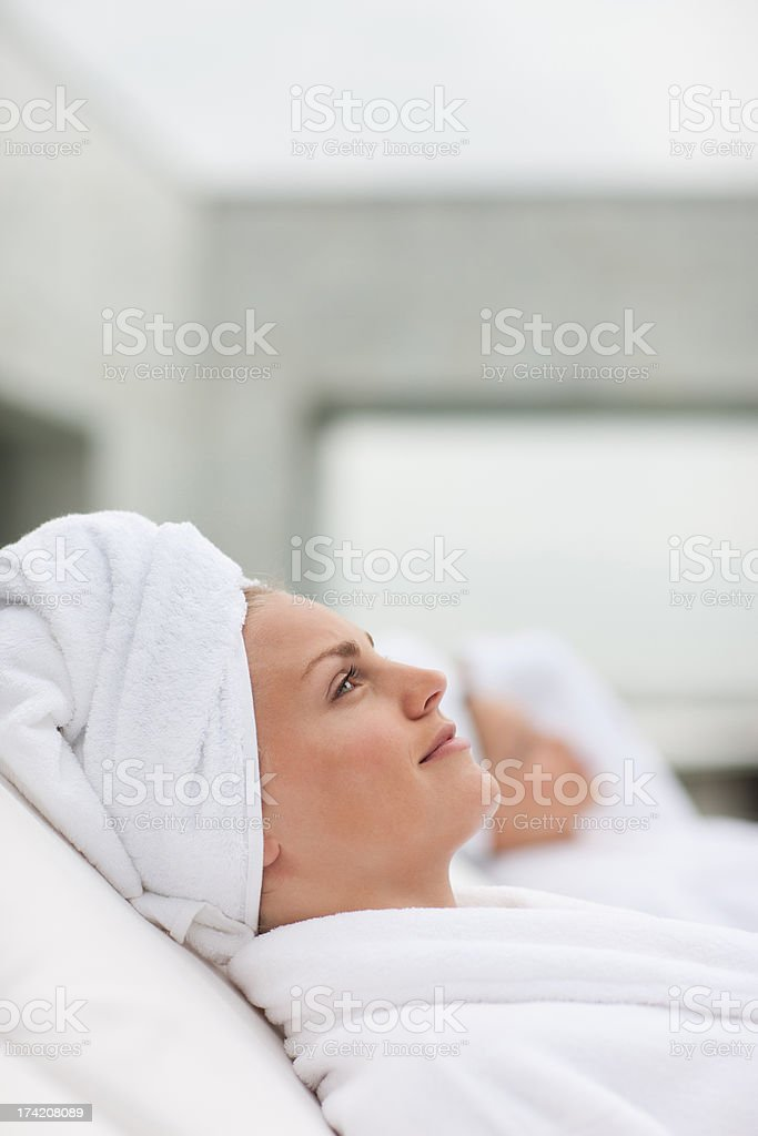 Women in bathrobes laying in lounge chairs stock photo