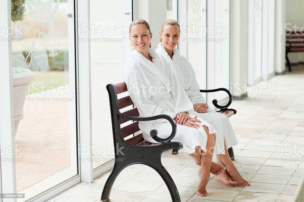 Women in bathrobes sitting on bench poolside at spa royalty-free stock photo