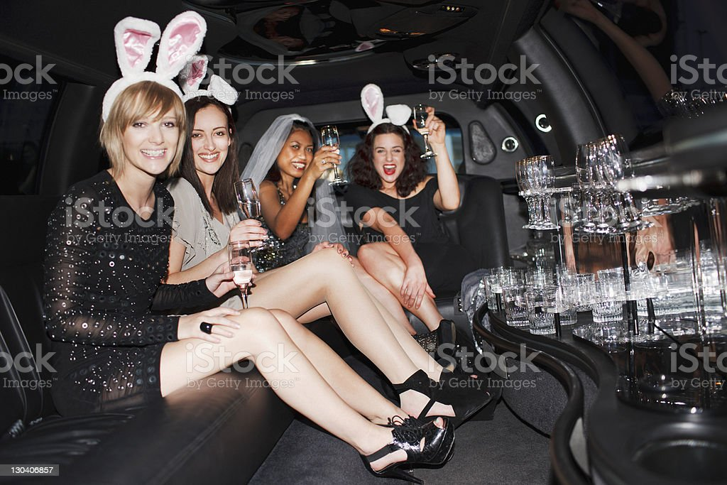 Women in bunny ears drinking champagne in limo stock photo