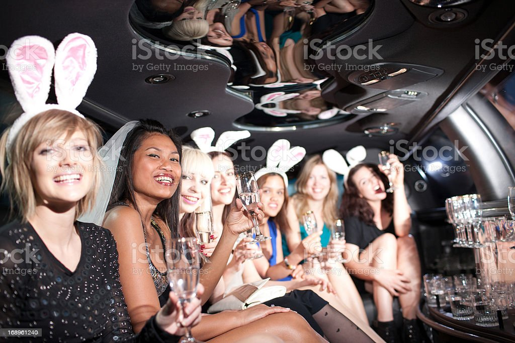 Women in bunny ears toasting in back of limo stock photo