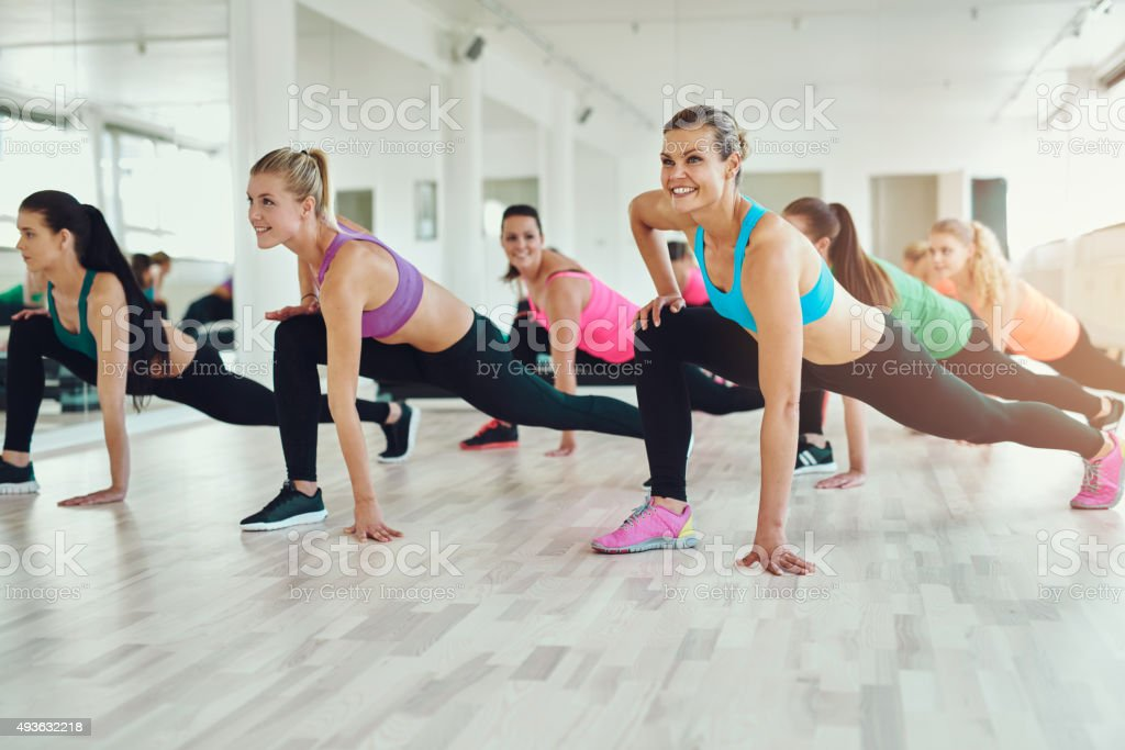 women in colourful sportswear exercising stock photo