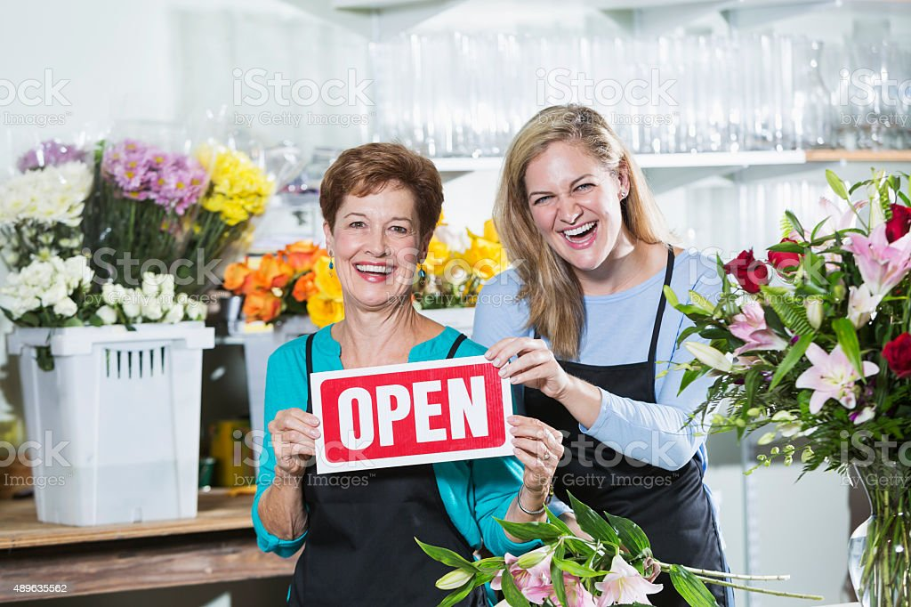 Flower shop open for business. A senior woman and her adult daughter...