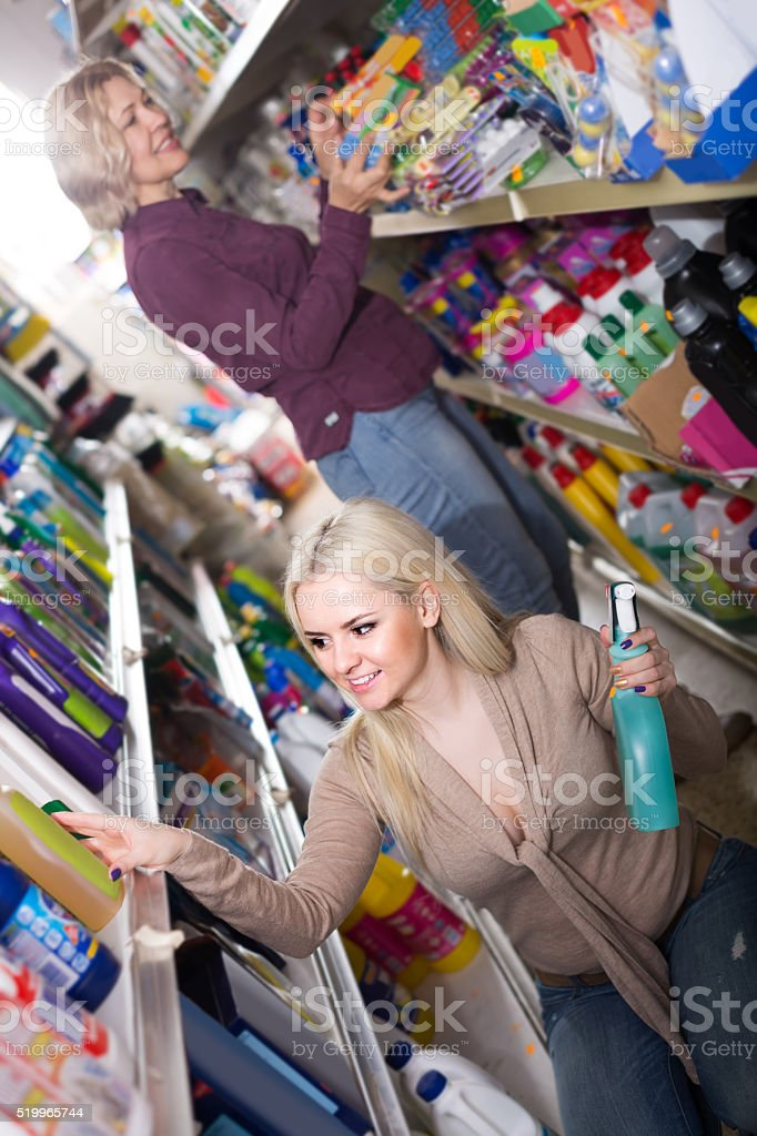women in good spirits selecting detergents in the store stock photo