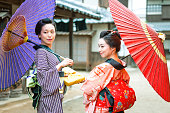 Women in kimono under umbrellas may look down the street