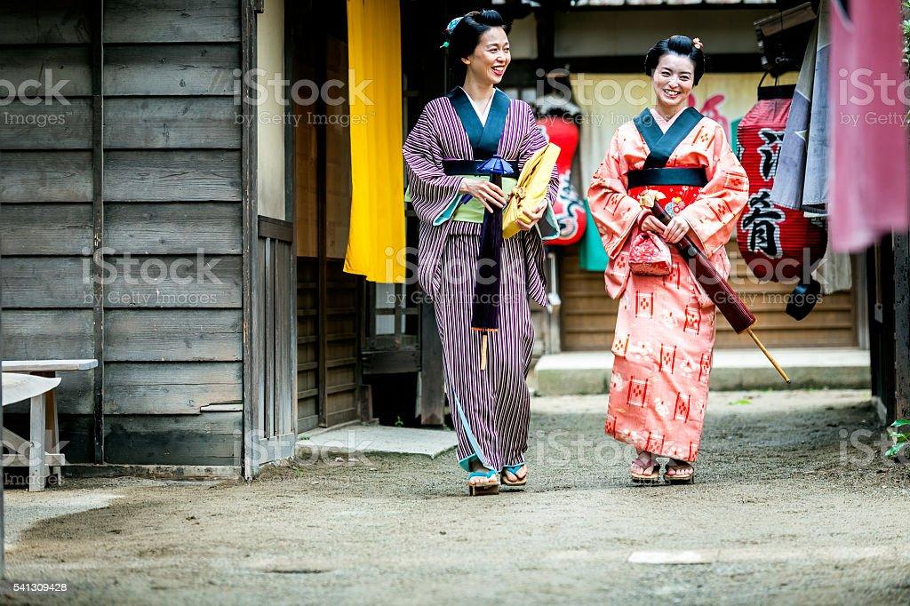 Women in kimono under umbrellas talk on the street, Japan stock photo
